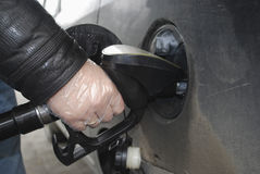 Man's hand holding a gun to the fueling of the car. Stock Photos