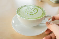 A man`s hand holding a hot matcha green tea cup Royalty Free Stock Photos