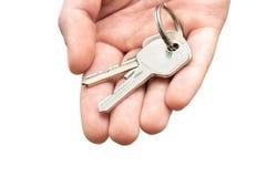 Hand holding keys. Man's hand holding house keys on white background Royalty Free Stock Photo