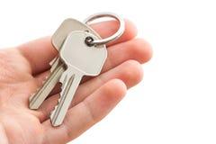Hand holding keys. Man's hand holding house keys on white background Royalty Free Stock Images