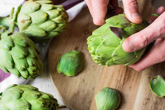 Man`s hand holding knife and peeling fresh artichokes, preparing for cooking, cutting board Royalty Free Stock Photography