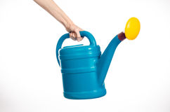Man's hand holding a large blue plastic watering can  on white  Royalty Free Stock Image
