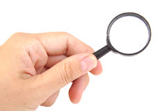 Man's hand holding magnifying glass, closeup Royalty Free Stock Photos