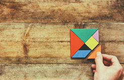 Man's hand holding a missing piece in a square tangram puzzle, over wooden table Royalty Free Stock Photo