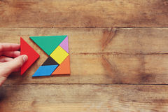 Man's hand holding a missing piece in a square tangram puzzle, over wooden table. Stock Images
