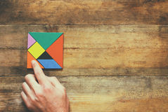 Man's hand holding a missing piece in a square tangram puzzle, over wooden table Royalty Free Stock Photos