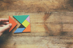 Man's hand holding a missing piece in a square tangram puzzle, over wooden table Royalty Free Stock Images