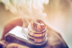 Man`s hand holding Mod for vaping, vape device and dripping RDA without top cap royalty free stock photos