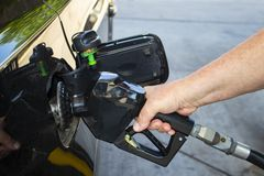 Man`s hand holding nozzle of gas pump and putting gas into black car stock photos