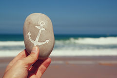 Man's hand holding one stone pebbles with theanchor sign  against sandy beach and sea horizone Royalty Free Stock Photos