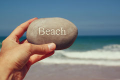 Man's hand holding one stone pebbles with theanchor sign  against sandy beach and sea horizone Stock Images