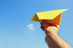 Man's hand holding paper airplane against blue sky Royalty Free Stock Image