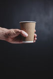 Man's hand holding a paper cup Stock Photo