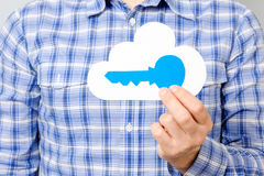 Man`s hand holding paper model of cloud and blue key. Cloud computing, technology, connectivity concept Royalty Free Stock Image