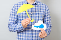 Man`s hand holding paper model of cloud and blue key. Man`s hand holding paper model of cloud with blue key and yellow umbrella. Cloud computing, technology Royalty Free Stock Photography