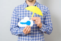 Man`s hand holding paper model of cloud and blue key Stock Images