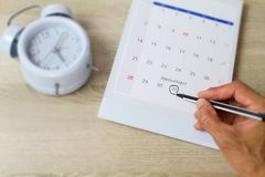 Man`s hand holding pen and marking on calendar on blurred blue classic alarm clock on vintage wooden table. Business concept royalty free stock images