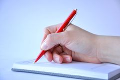 Man`s hand holding a pen and writing in a notebook stock photography
