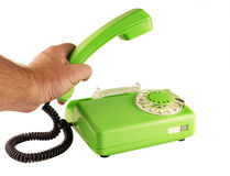 Man`s hand holding the phone with a rotary dial. On a white background male hand holding a green telephone handset rotary dialer stock photo