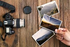 Man`s hand holding photo with old grunge camera and photos on vintage grunge wooden background Royalty Free Stock Images