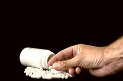 Man's hand holding pill from tablet bottle. Medical concept Royalty Free Stock Photo