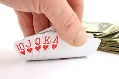 Man's hand holding a royal flush with cash Royalty Free Stock Photos