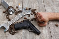 A man`s hand holding rusty chain, next to are dangerous weapons, cigarettes, a wrench and a flashlight. royalty free stock photography