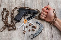 A man`s hand holding rusty chain, next to pistol, a few ammunition, a knife and cigarettes. A man`s hand holding an old rusty chain, next there is a black Royalty Free Stock Images