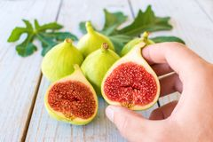 Man`s hand holding a sliced fig. Over a wooden table Royalty Free Stock Image