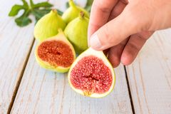 Man`s hand holding a sliced fig. Over a wooden table Stock Images