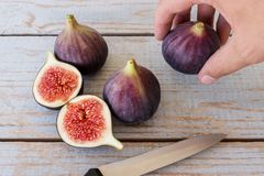 Man`s hand holding a sliced fig. Over a wooden table Royalty Free Stock Photo