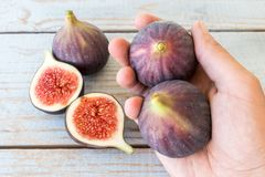 Man`s hand holding a sliced fig. Over a wooden table Royalty Free Stock Photos