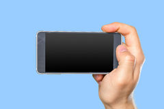 Man's hand holding smartphone Stock Images
