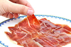 Man's hand holding an spanish serrano ham slice. Stock Photography