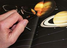 Man`s hand holding spectacles on photo of planets. A male hand holding spectacles and resting on the page of a book depicting the planets Saturn and Jupiter with Stock Photo