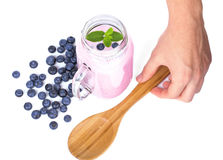 Man`s hand holding a spoon. Berry products isolated on a white background. Natural blueberry milkshake in a mason jar. Stock Image