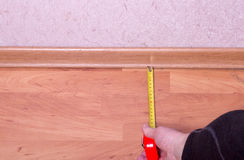 Man's hand holding a tape measure on a wooden floor Stock Photography