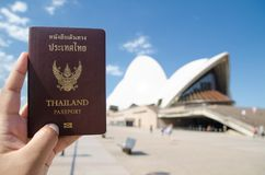 A man`s hand holding Thailand passport with blurred background of Sydney Opera House for Concepts of traveling. SYDNEY, AUSTRALIA. – On December 14, 2017 royalty free stock photo