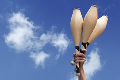 Man's hand holding three wooden juggling clubs in the blue sky Stock Image