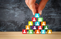 Man& x27;s hand holding a top of wooden blocks pyramid with people icons over wooden table. Man& x27;s hand holding a top of wooden blocks pyramid with Royalty Free Stock Images