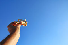 Man's hand holding toy airplane against the sky Stock Photos