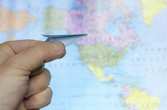 Man`s hand holding toy paper airplane against map of the world Royalty Free Stock Image