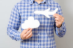 Man`s hand holding white paper model of plane and cloud Royalty Free Stock Photo
