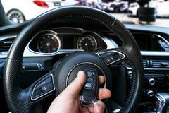 Man`s hand holding a wireless car key in black leather interior. Modern Car interior details. Car detailing. Car inside. Car deta. Iling royalty free stock photos