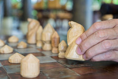 Man's hand holding wooden chess to check match Royalty Free Stock Photo