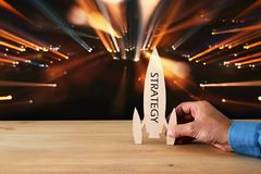 man& x27;s hand holding wooden rocket with word - strategy - over glitter black background. Stock Photo