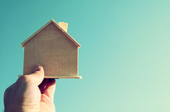 Man's hand holding a wooden toy house against blue sky Royalty Free Stock Images