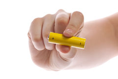 Man's hand holding a yellow battery or battery on a white background isolated. Battery from Ikea. Photo fits the theme of ecology or problems Greenpeace or Stock Photography