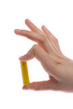 Man's hand holding a yellow battery or battery on a white background isolated. Battery from Ikea. Photo fits the theme of ecology or problems Greenpeace or Royalty Free Stock Photo