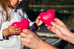Man's hand holds baby Two red plastic heart stock photo